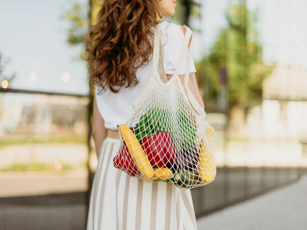 Woman in white dress holding mesh bag full of produce.