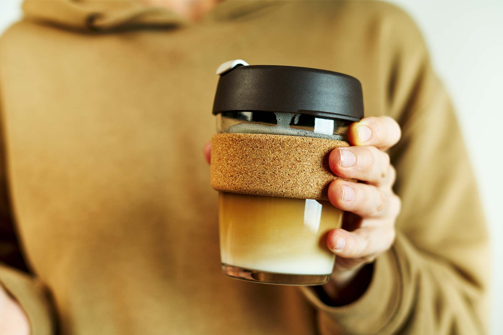 Woman in brown sweater holding best eco friendly travel mug.