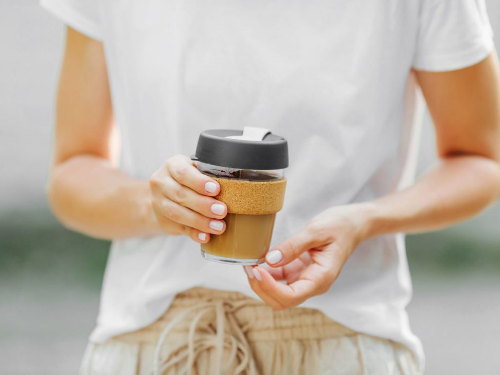 Woman in white shirt holding glass reusable coffee mug
