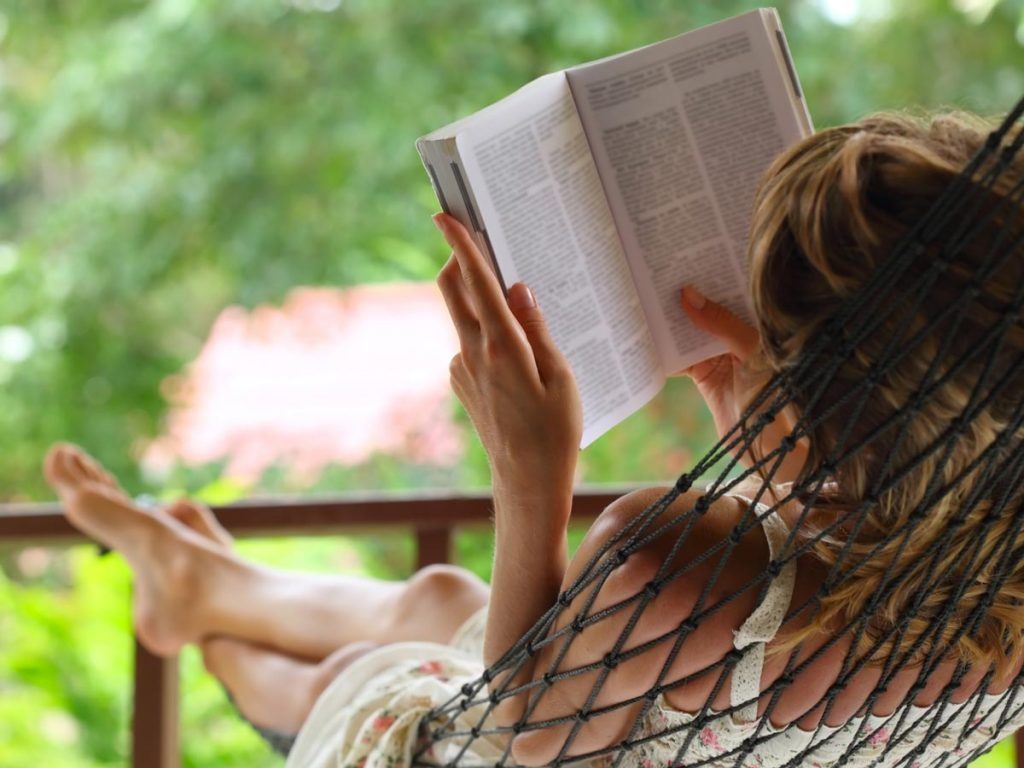 Woman sitting in outdoor hammock reading book on sustainability.