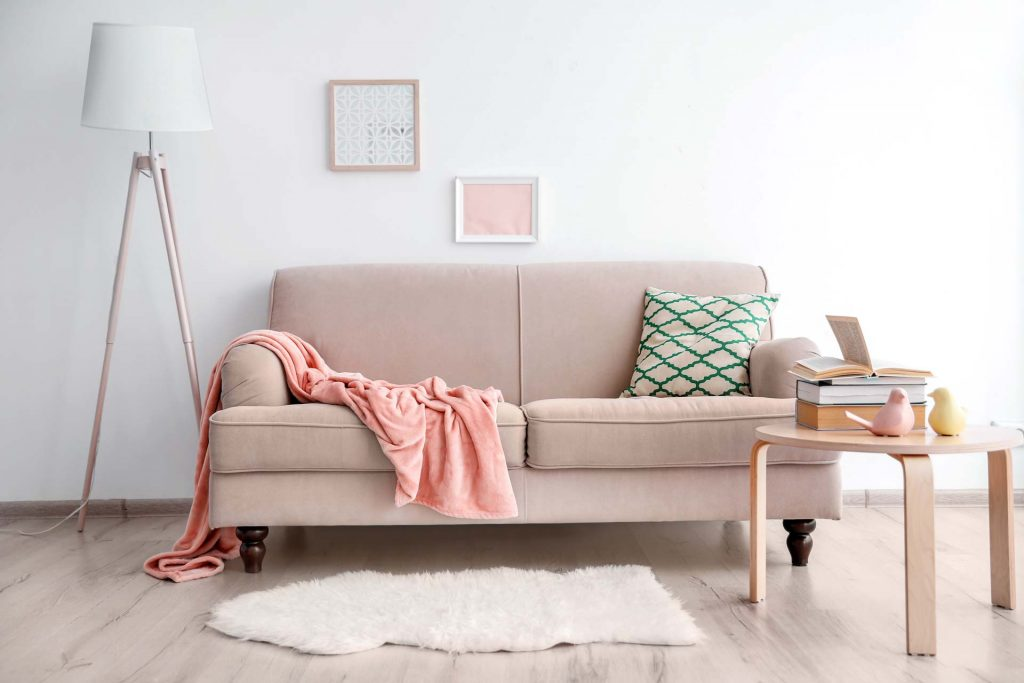 Pink couch, white lamp, and wood table arranged using principles of minimalism for beginners.