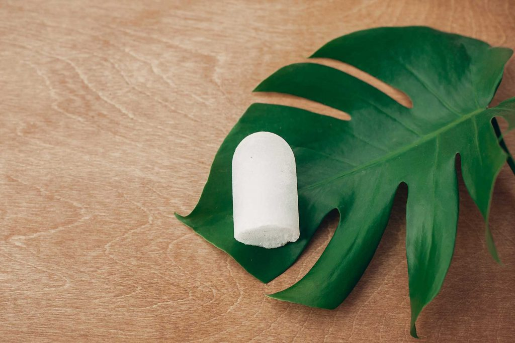 White plastic free deodorant bar on top of large green leaf.