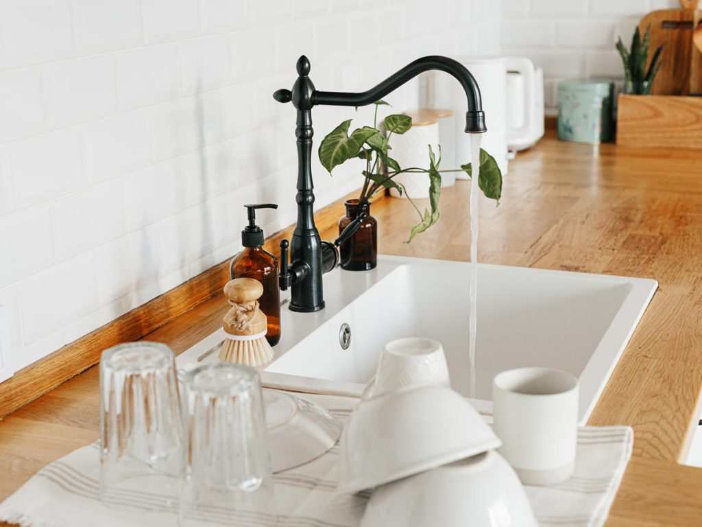 Zero waste kitchen sink counter with stack of white and glass dishes on tea towel.