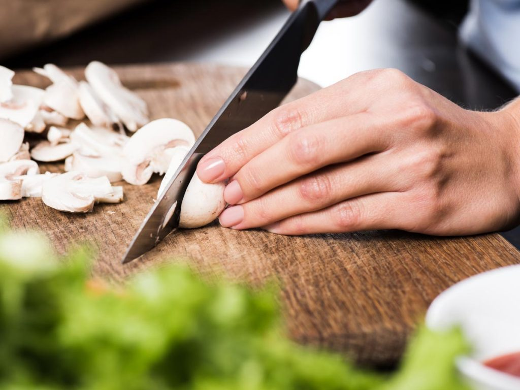 Close up of person cutting mushrooms on a wooden cutting board.