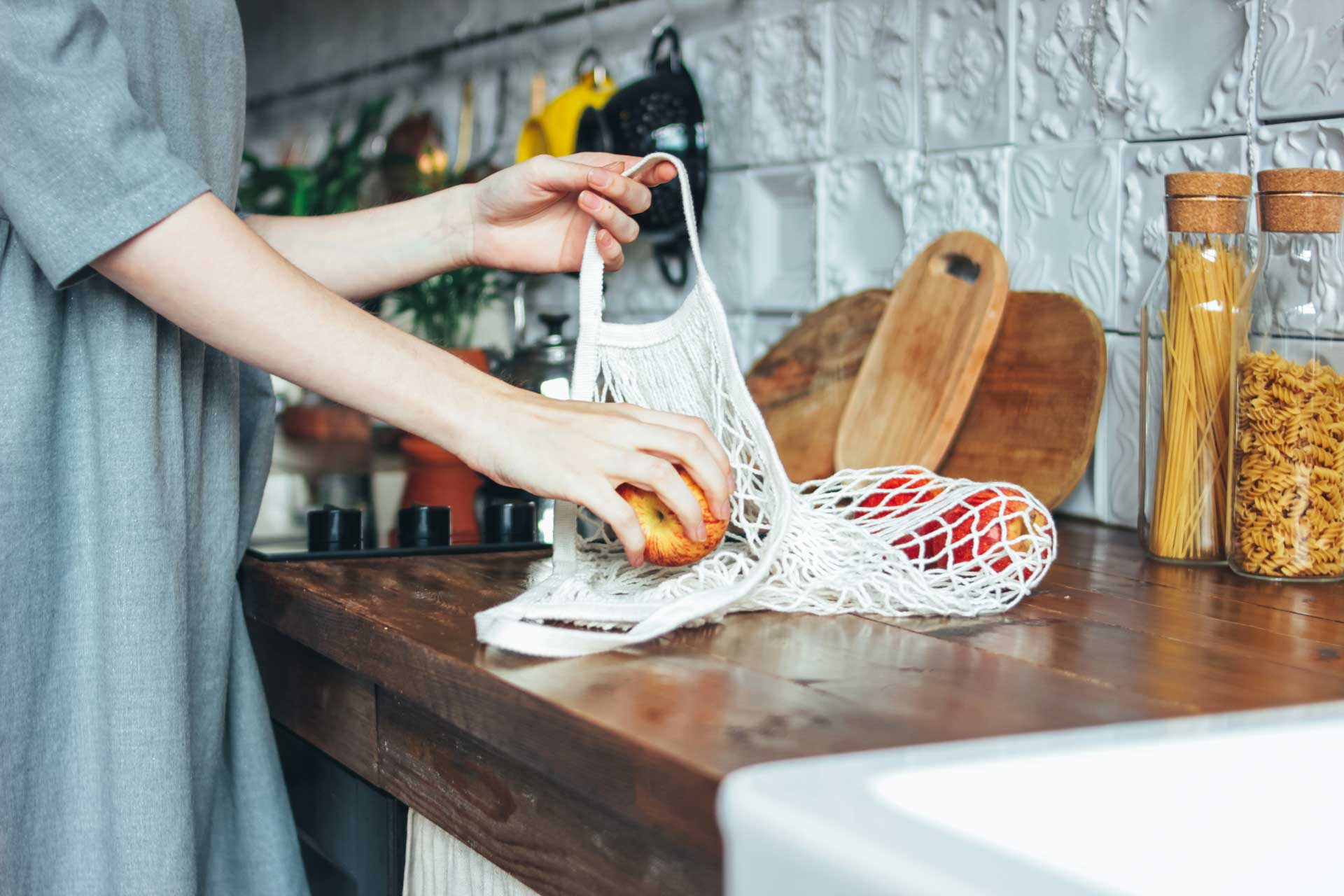 Woman in zero waste kitchen putting apples into mesh bag.