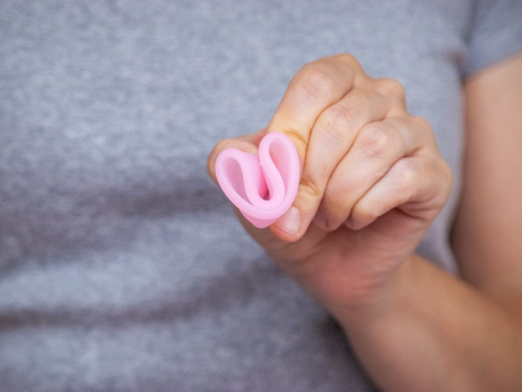 Woman holding pink menstrual cup in c fold.