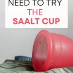 """Pink menstrual cup on top of green fabric, with text overlay - """"why you need to try the Saalt cup""""."""