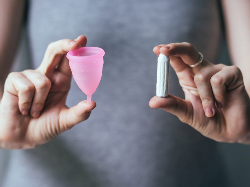 Woman holding a pink menstrual cup and a tampon in each hand.