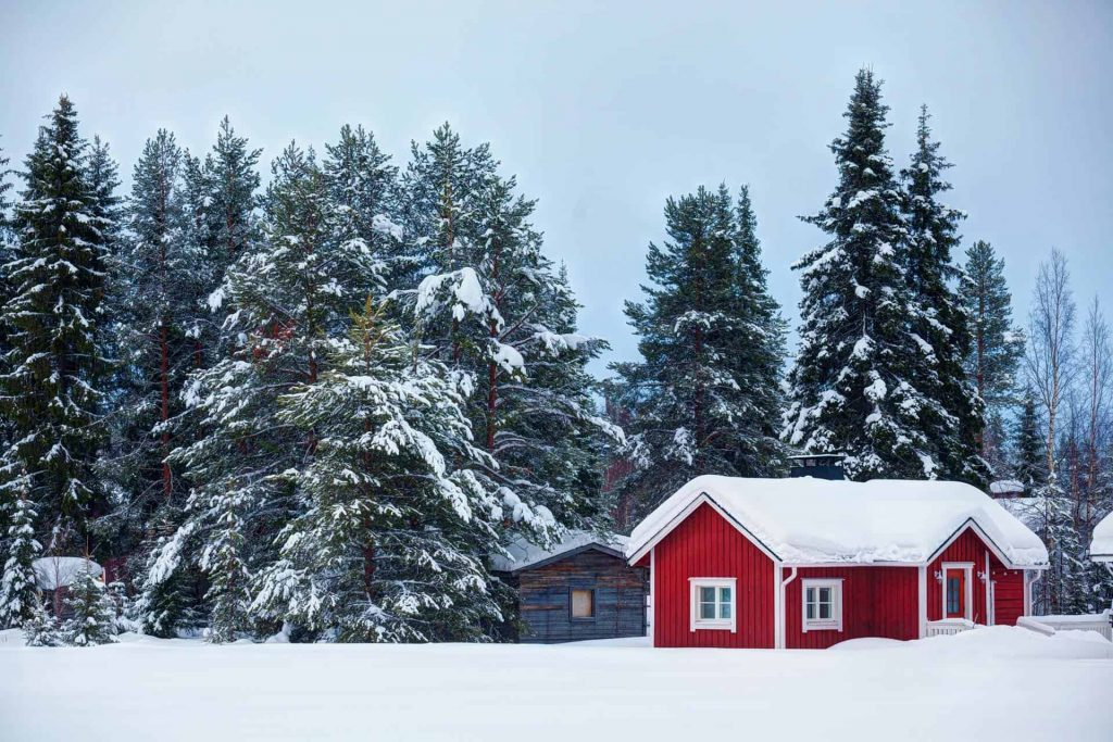 Red cottage in snowy forest landscape, an idyllic place to move to live a simple life.