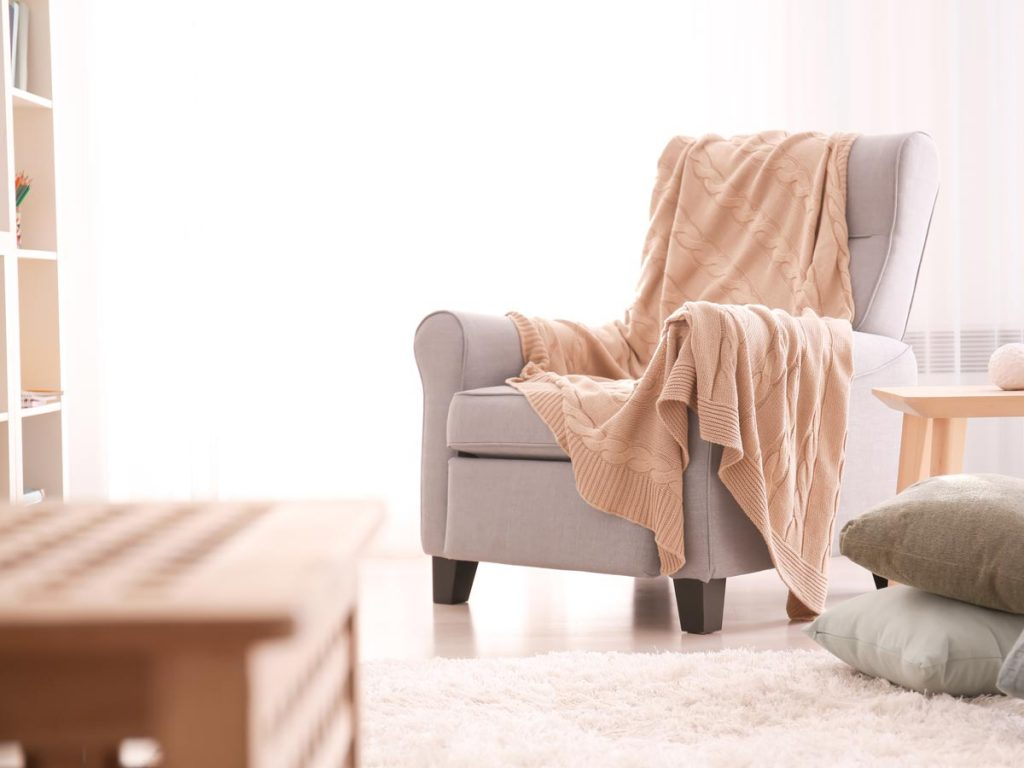 Bright living room with grey chair and pink throw blanket.