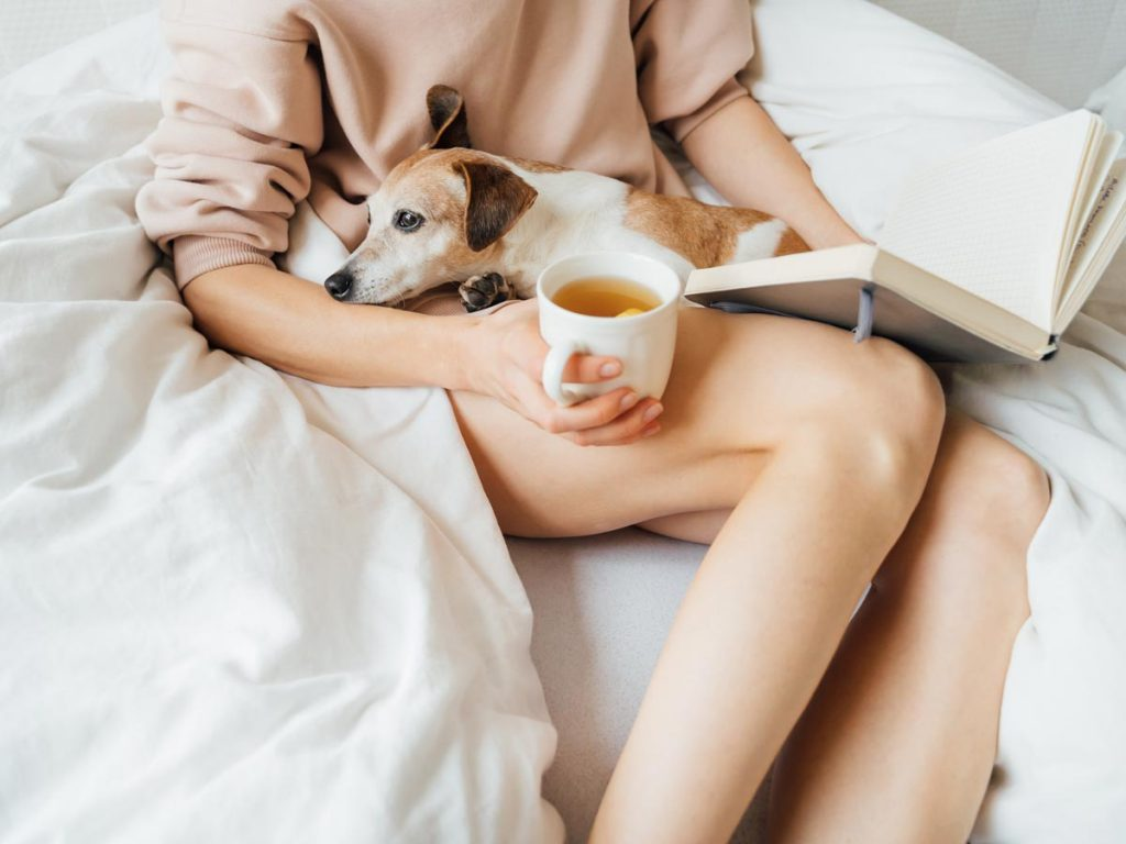 Woman relaxing on bed with dog and tea in lap.