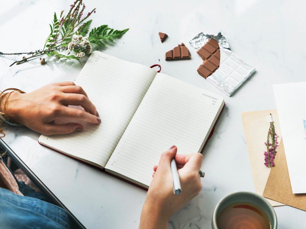 Woman writing in blank journal.