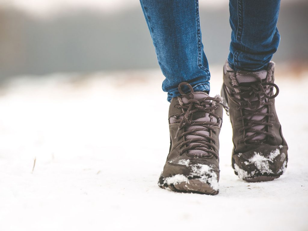 Person wearing sustainable winter boots walking through snowy field.
